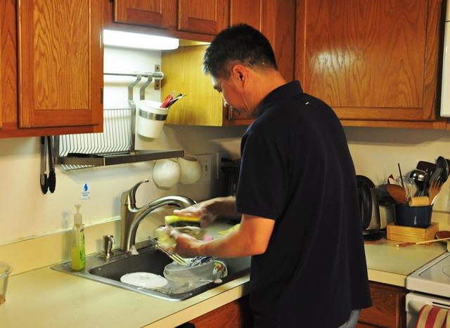 Osin đang rửa bát. Ảnh: HM