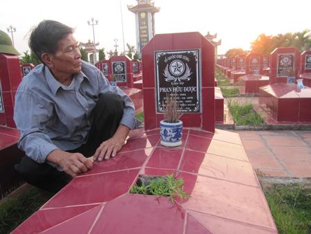 Ông Phan Hữu Được bên cạnh mộ của mình. Ảnh: Dân Trí.