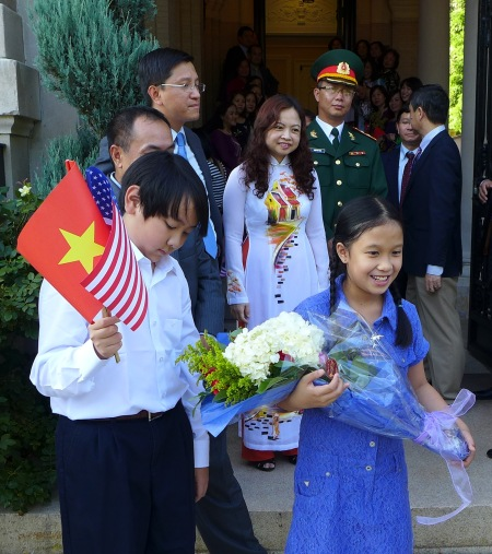 Các cháu tập tặng hoa và nói tiếng Việt. Ảnh: HM