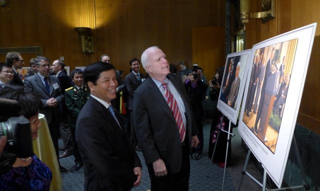 Đs. Nguyễn Quốc Cường đưa John McCain thăm tranh triển lãm. Ảnh: HM