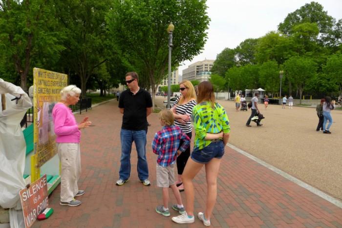 Bà cụ biểu tình đang nói chuyện với khách du lịch. Ảnh: HM chụp chiều nay.