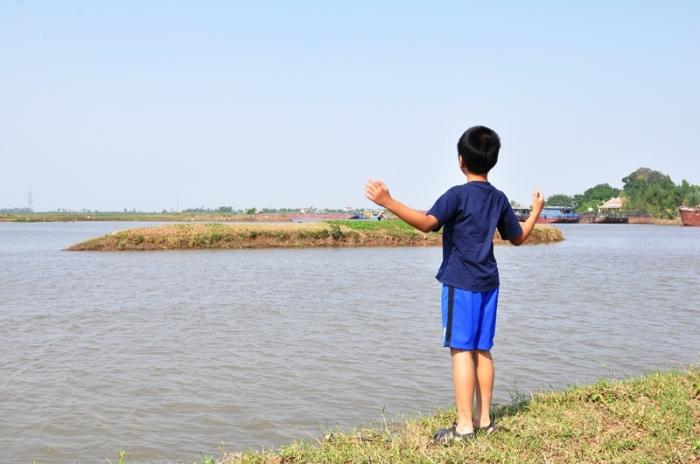 Chỗ cu Bin đứng là nhà cũ của cụ Sỡi, cụ Du, mom đất giữa sông là nhà lão Cua. Ảnh: HM